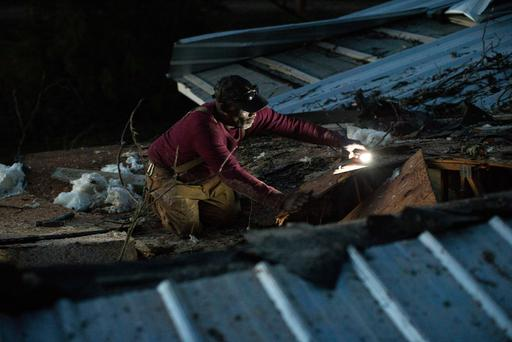 Terry Paramore works on his roof after a severe storm caused a tree to fall on his home. (AP Photo/Branden Camp)
