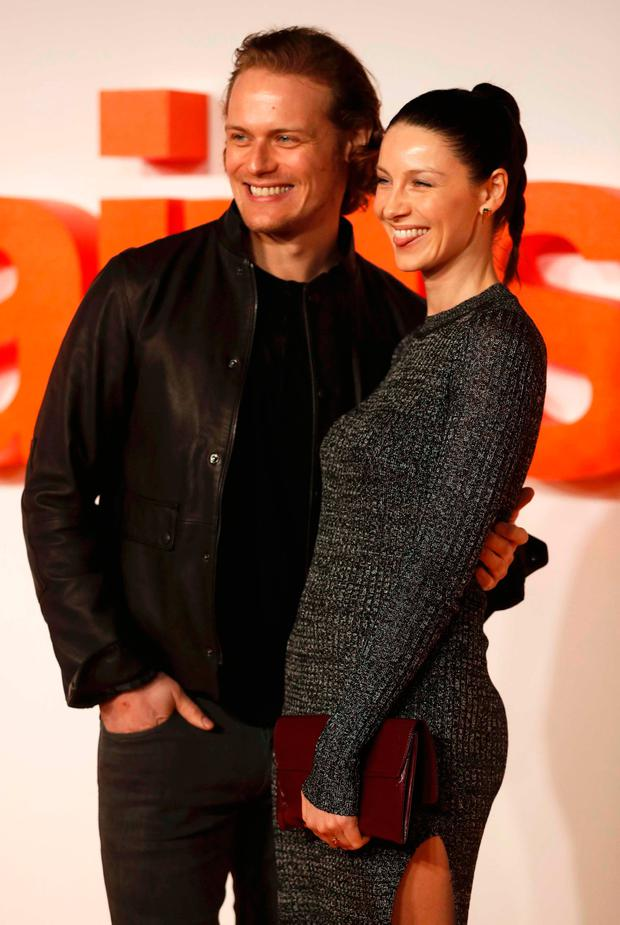 Actors Sam Heughan and Caitriona Balfe (R) pose as they arrive at the world premiere of the film
