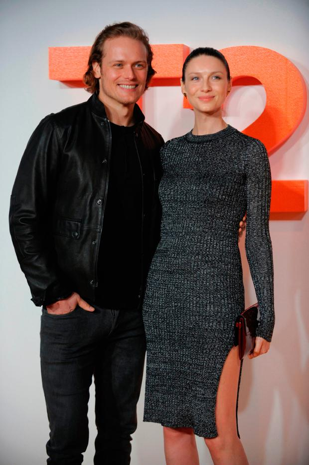 Irish actress and model Caitriona Balfe (R) poses with British actor Sam Heughan (L) on the red carpet arriving to attend the world premiere of the film T2 Trainspotting in Edinburgh