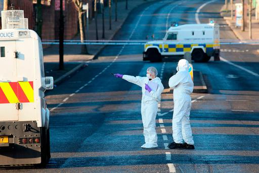 Police forensics officers examine the area around a sealed-off petrol station in north Belfast following the shooting of a police officer. Photo: AFP/Getty Images