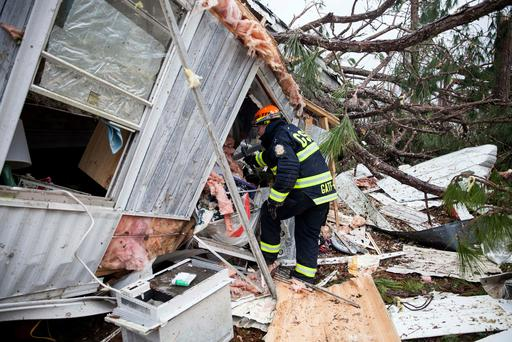 A rescue worker enters a hole in the back of a mobile home in Big Pine Estates that was damaged by a tornado (Photo: AP Photo)