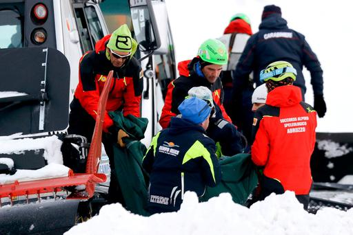 Rescuers carry away the body of one of the victims. Photo: Gregorio Borgia/AP