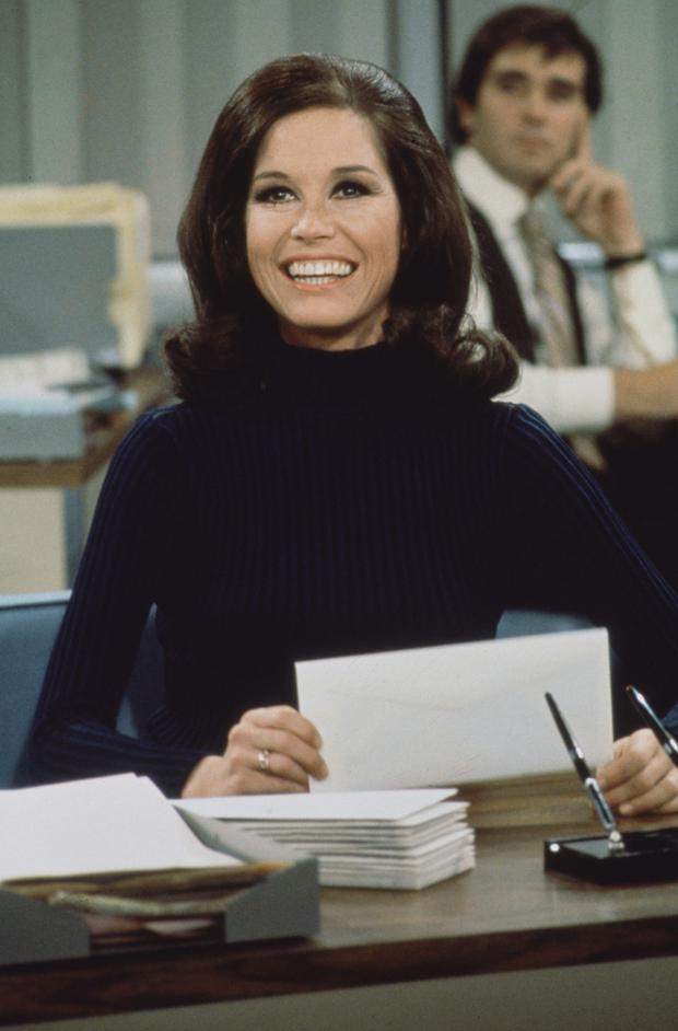 American actress and commediene Mary Tyler Moore (as Mary Richards) smiles broadly as she sits at a desk in a scene from 'The Mary Tyler Moore Show' (also known as 'Mary Tyler Moore'), Los Angeles, California, 1970. (Photo by CBS Photo Archive/Getty Images)