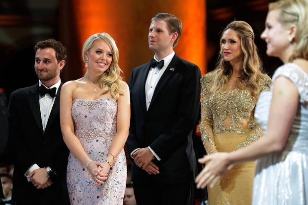 (L-R) Tiffany Trump (2nd L) and her guest Ross Mechanic (L), and Eric Trump and his wife Lara Yunaska watch as U.S. President Donald Trump cuts a cake during the inaugural Armed Services Ball at the National Building Museum January 20, 2017 in Washington, DC.