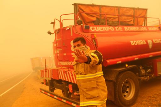 A firefighter gestures while standing near his firetruck as the worst wildfires in Chile's modern history ravaged wide swaths of the country's central-south regions, in Santa Olga, Chile January 26, 2017. REUTERS/Pablo Sanhueza EDITORIAL USE ONLY. NO RESALES. NO ARCHIVE.
