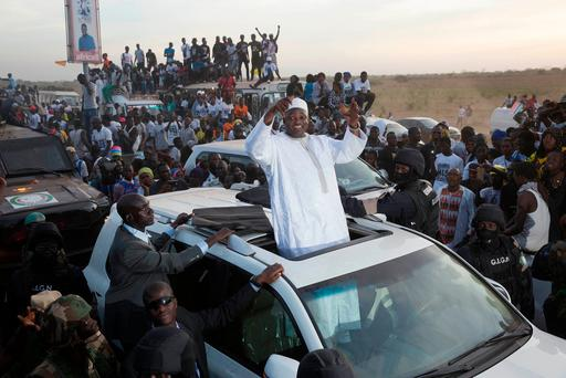 Gambian President Adama Barrow waves as he rides his motorcade through crowds of hundreds of thousands after arriving at Banjul airport in Gambia after flying in from Dakar, Senegal. Photo: AP