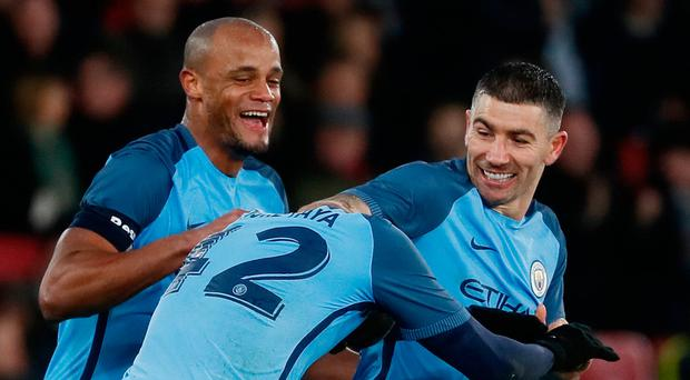 Manchester City's Yaya Toure celebrates scoring their third goal with Aleksandar Kolarov and Vincent Kompany. Photo: Stefan Wermuth/Reuters