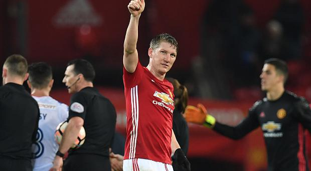 Manchester United's German midfielder Bastian Schweinsteiger (C) salutes the crowd