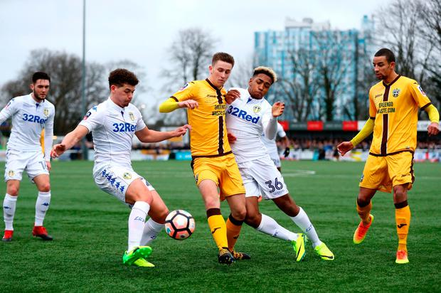 Adam May of Sutton United (C) and Tyler Denton of Leeds United (R) battle for possession. Photo by Bryn Lennon/Getty Images