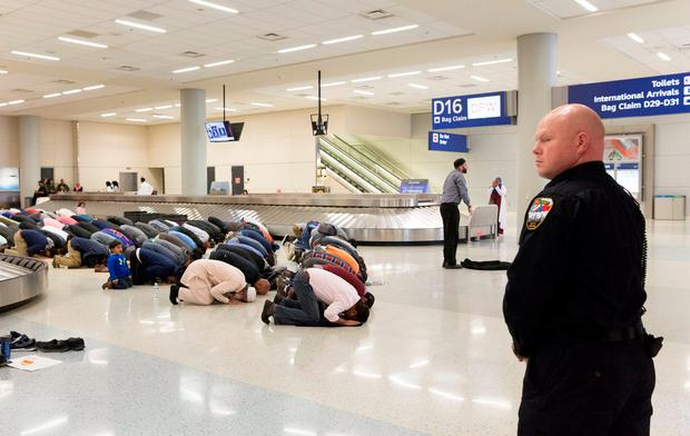 People gather to pray in the baggage hall at Dallas/Fort Worth airport. Photo: Reuters.