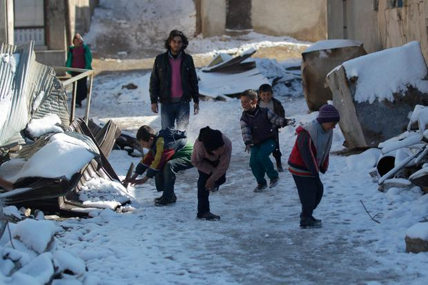 Children play with snow near to the rubble of buildings in al-Rai town, northern Aleppo. Photo: Reuters