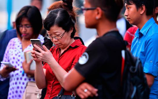 Chen Peijie, China's consul-general in Sabah, checks her mobile phone at a jetty in Kota Kinabalu as she awaits news. Photo: AFP/Getty