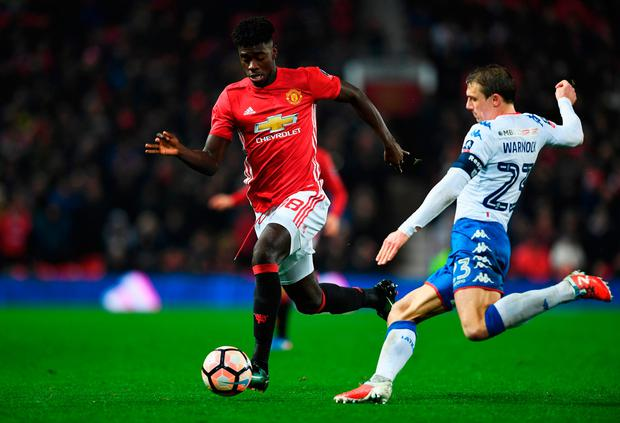 Axel Tuanzebe of Manchester United is tackled by Stephen Warnock of Wigan Athletic. Photo by Gareth Copley/Getty Images