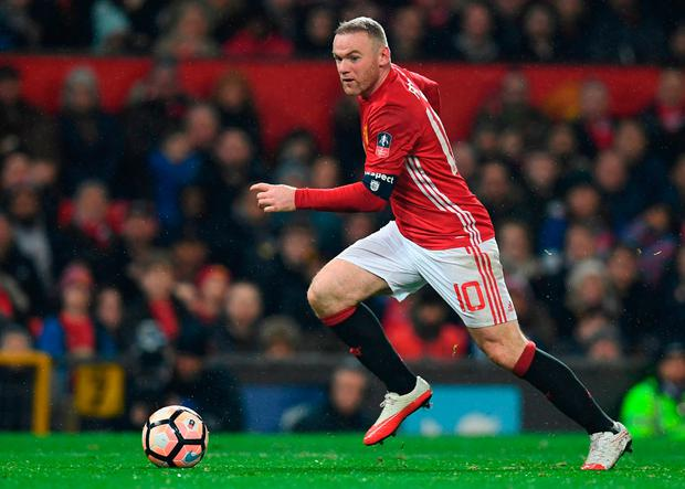 Manchester United's English striker Wayne Rooney runs with the ball. Photo: Getty Images