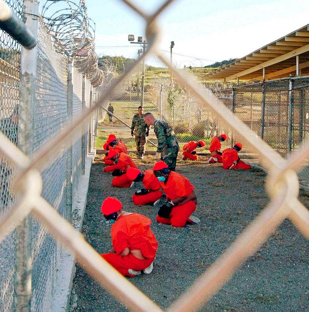 Detainees kneeling in a holding area at the US military prison at Guantanamo Bay Cuba in 2002