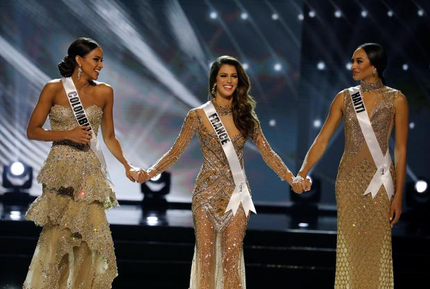 Miss France Iris Mittenaere (C) holds hands with other finalists Miss Haiti Jacque Pellisier (R) and Miss Colombia Andrea Tovar, shortly before Mittenaere won the 65th Miss Universe beauty pageant at the Mall of Asia Arena, in Pasay, Metro Manila, Philippines January 30, 2017. REUTERS/Erik De Castro