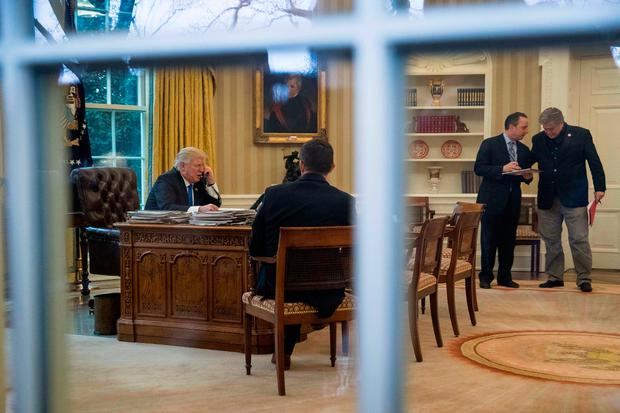 President Donald Trump, accompanied by Chief of Staff Reince Priebus, second from right, and White House Senior Advisor Steve Bannon, right, speaks on the phone with German Chancellor Angela Merkel, Saturday, Jan. 28, 2017, in the Oval Office at the White House in Washington. (AP Photo/Andrew Harnik)
