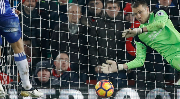Liverpool goalkeeper Simon Mignolet gets down to save Diego Costa's penalty. Photo: Reuters