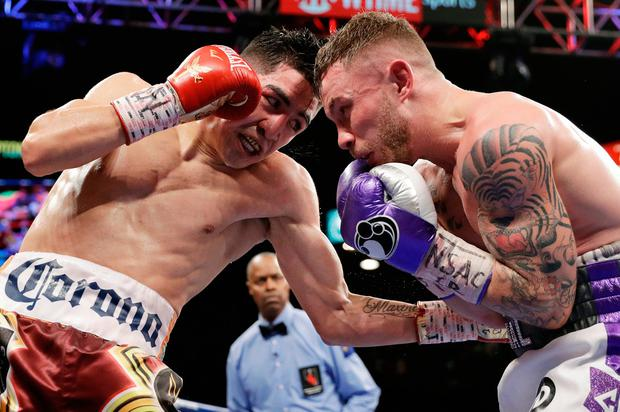 Leo Santa Cruz, left, hits Carl Frampton during their featherweight title boxing match. Photo: AP