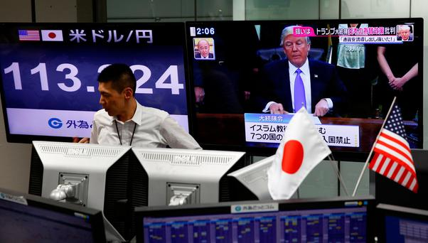 An employee of a foreign exchange trading company stands in front of a TV monitor showing US President Donald Trump and another monitor showing the Japanese yen's exchange rate against the US dollar in Tokyo. Photo: Reuters