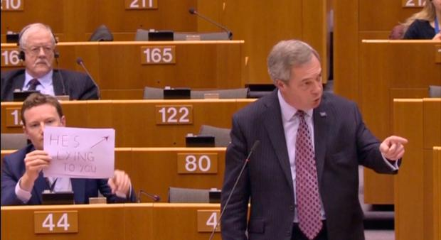 Labour MEP Seb Dance holds a sign that reads 'He's lying to you' behind Nigel Farage as he addresses the European Parliament Photo: European Parliament/EBS/Handout via REUTERS TV