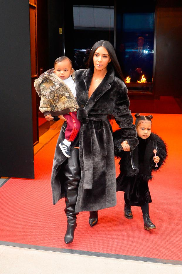 (L to R) Saint West, television personality Kim Kardashian West, and North West leave their Midtown Manhattan hotel on February 1, 2017 in New York City. (Photo by Raymond Hall/GC Images)