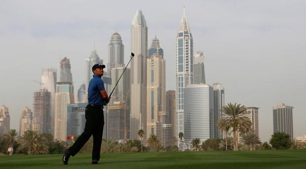 Tiger Woods follows his ball on the 13th hole during the Dubai Desert Classic