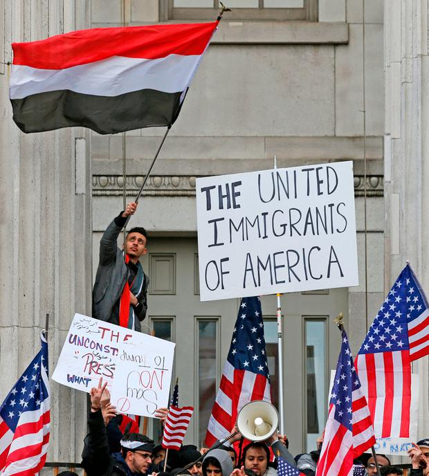 A man waves a Yemeni flag as he and other members of the Yemeni community were joined by a huge crowd of supporters during a protest on the steps of Brooklyn's Borough Hall (AP Photo/Kathy Willens)