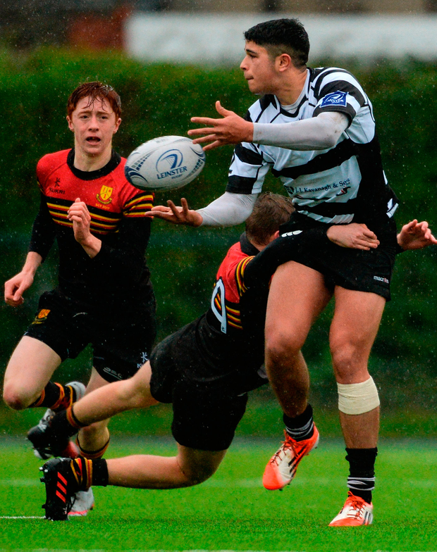 Adi Donavan of Cistercian College Roscrea is tackled by Robert Ivers of CBC Monkstown, supported by team-mate Shane O'Hanrahan. Photo: Piaras Ó Mídheach/Sportsfile