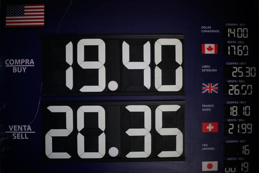 A board displaying exchange rates is seen at a foreign exchange house in Mexico City