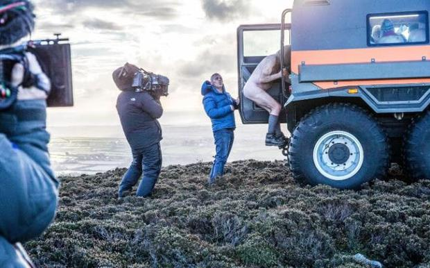 The Top Gear presenter helps a naked rambler board an Avtoros Shaman during filming on the Isle of Man Credit: David Venni/PA/BBC
