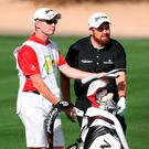 Shane Lowry of Ireland stands with his bag and caddie on the ninth hole