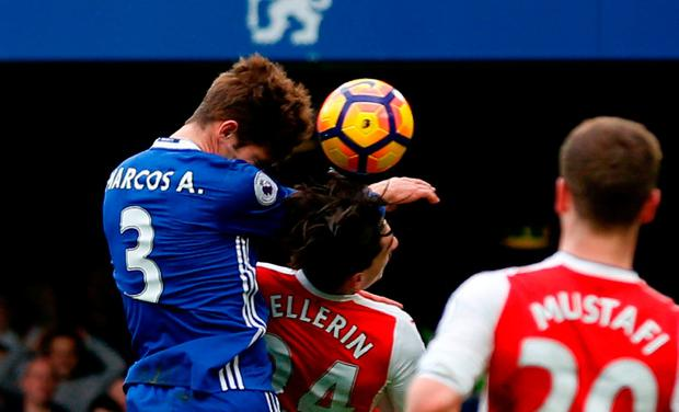 Chelsea's Spanish defender Marcos Alonso (L) rises above Arsenal's Spanish defender Hector Bellerin (C) to score the opening goal during the English Premier League football match between Chelsea and Arsenal at Stamford Bridge