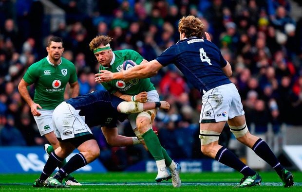 Jamie Heaslip of Ireland is tackled by Zander Fagerson, left, and Richie Gray of Scotland