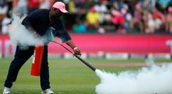 Head groundsman of Wanderers stadium, Bethuel Buthelezi uses a fire extinguisher on bees that invaded the pitch. Photo: Siphiwe Sibeko/Reuters