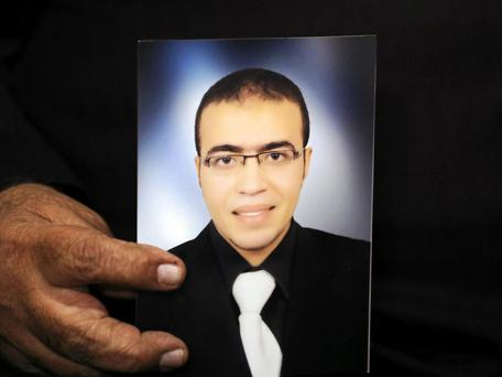 Reda Abdullah al-Hamamy, the father of Abdullah Reda al-Hamamy who is suspected of attacking a soldier in Paris' Louvre museum, holds a picture of his son. Photo: Reuters