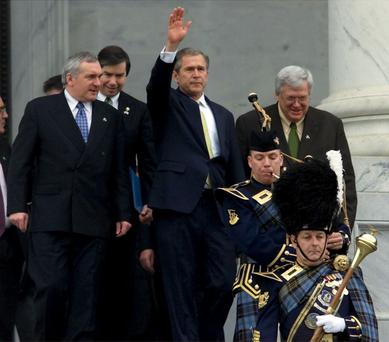 U.S. President George W. Bush waves to supporters as he walks with Irish Prime Minister Bertie Ahern (L) and U.S. Speaker of the House Dennis Hastert (R) from the U.S. Capitol, March 15, 2001.