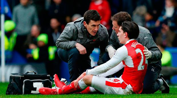 Arsenal's Hector Bellerin receives attention on the pitch after clashing in the air with Chelsea's Marcos Alonso