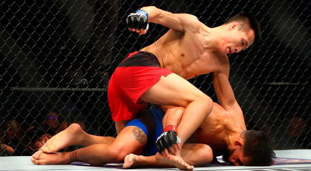 Chan Sung Jung (blue gloves) defeats Dennis Bermudez by knockout