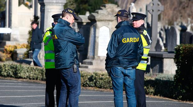 Gardai and Detectives keep watch at near the grave of David Byrne at Mount Jerome cemetery in Harolds Cross Dublin, today is the one year anniversary of his shooting at the regency Hotel.