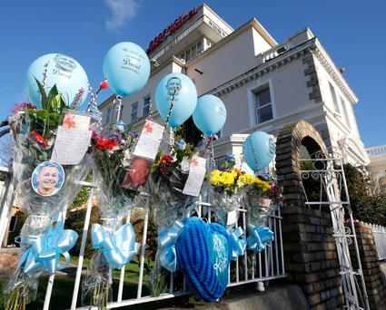 Flowers and balloons hanging next to the Regency Hotel in memory of David Byrne.