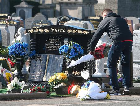 A young man leaves flowers at the grave of David Byrne at Mount Jerome cemetery in Harold's Cross Dublin.