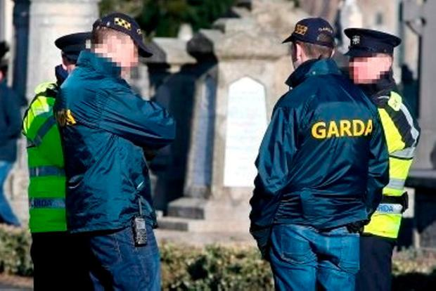 Gardaí and detectives keep watch near the grave.