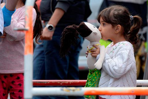 A refugee girl kisses her doll at a train station in Munich, Germany, in 2015. Photo: Getty