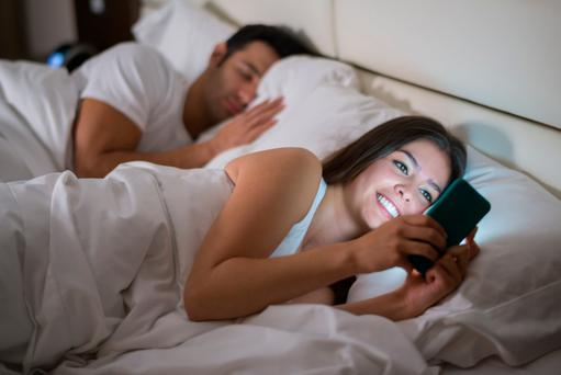 Woman texting on her phone in bed while her husband is sleeping