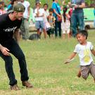 England football superstar David Beckham (L) chases a boy during a football game with children-survivors of super Typhoon-Haiyan at a school ground in Tanuan town, Leyte province, central Philippines on February 14, 2014, Photo: TED ALJIBE/AFP/Getty Images
