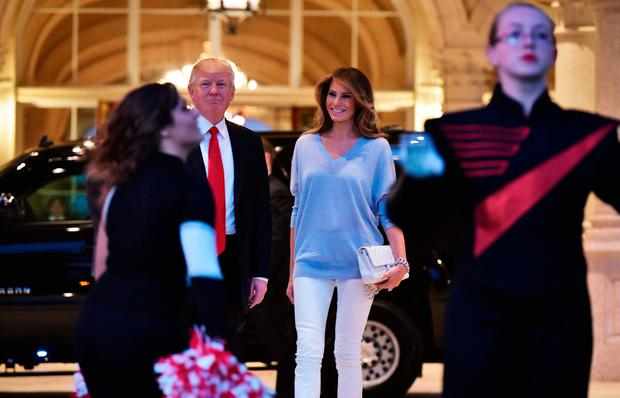 US President Donald Trump and First Lady Melania Trump watch the Palm Beach Central High School marching band perform as it greets them upon arrival to watch the Super Bowl at Trump International Golf Club Palm Beach in West Palm Beach, Florida on February 5, 2017. / AFP PHOTO / MANDEL NGANMANDEL NGAN/AFP/Getty Images