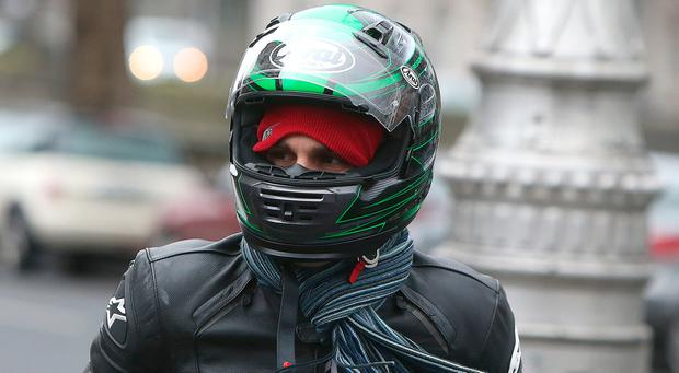 Christian Carter arrives at the High Court in Dublin wearing a motorcyle helmet. Photo: Damien Eagers