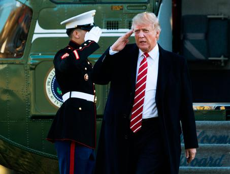 President Donald Trump salutes a Marines honor guard as he disembarks from Marine One upon arrival at the White House in Washington. (AP Photo/Manuel Balce Ceneta)