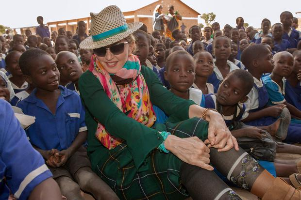 US pop diva Madonna sits among Malawian children during a visit to the Mkoko Primary School, one of the schools Madonna's Raising Malawi organization has built jointly with US organization BuildOn in the Kasungu District, Central Malawi, on November 30, 2014.